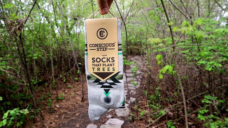 Socks That Give Back Held Up in a Forrest