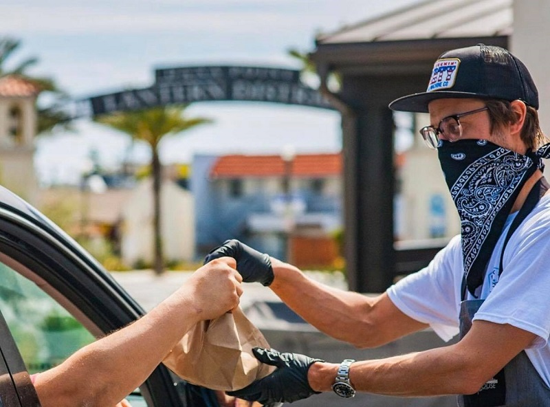 Bracken's Kitchen Feeding Orange County Man Handing Bag of Food to a Person in a Car