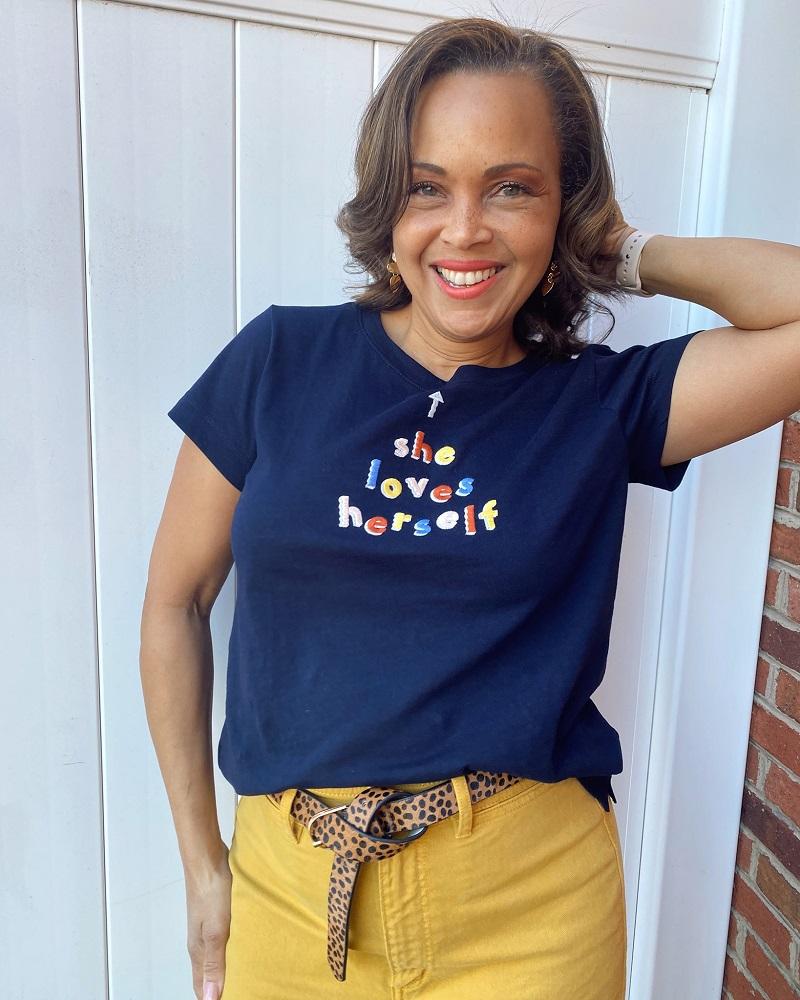Fashionable Good Deeds Woman Standin in a Doorway Wearing a Ciara Designer Shirt