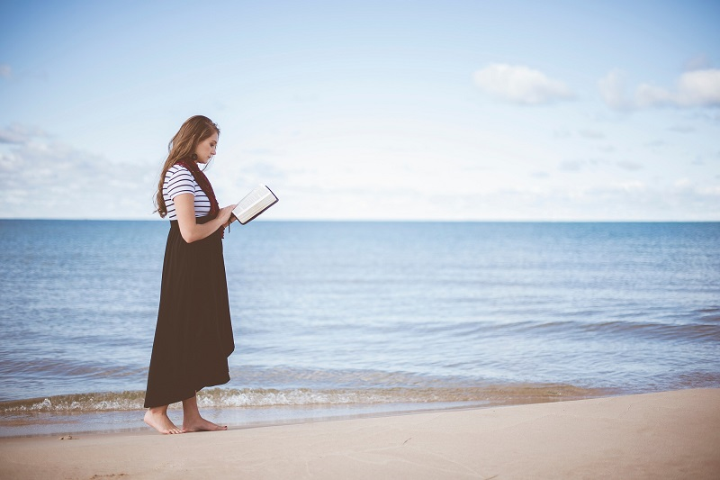 Good Deeds to do at the Beach Woman Walking on a Beach Reading a Book