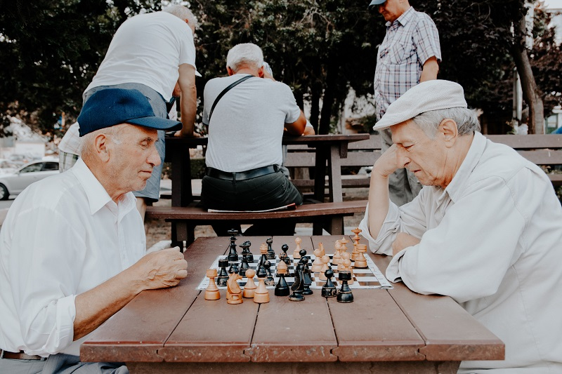 Good Deeds for Teens to Do During Summer Two Elderly Men Playing Chess at a Park